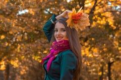 桃红色头巾的年轻逗人喜爱的女孩举了他的有叶子的手在她的头和微笑上 库存照片