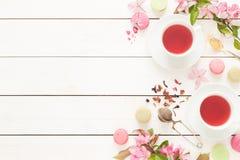 桃红色水果的茶和淡色法国macarons蛋糕在白色 库存图片