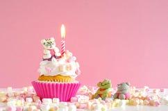 桃红色黄油奶油杯形蛋糕用蛋白软糖和蜡烛 免版税库存图片