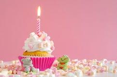 桃红色黄油奶油杯形蛋糕用蛋白软糖和蜡烛 库存图片