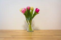 桃红色黄色郁金香木表白色墙壁玻璃花瓶 免版税库存照片