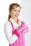 桃红色appron藏品符号广告牌的愉快的妇女。 免版税库存照片
