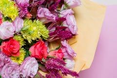 桃红色eustoms,一朵黄色菊花,一朵红色和桃红色玫瑰美丽的花束,在桃红色背景 免版税库存照片