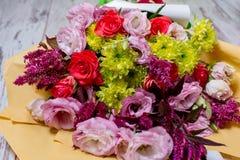 桃红色eustoms,一朵黄色菊花,一朵红色和桃红色玫瑰美丽的花束,在破旧的白色木背景 库存照片