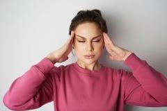 桃红色hoody的少妇与严厉头疼用在头的手在背景的白色空的墙壁 beauvoir 库存照片