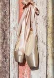 桃红色pointe鞋子,在老木背景的芭蕾舞鞋 库存图片