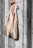 桃红色pointe鞋子,在老木背景的芭蕾舞鞋 免版税库存图片
