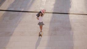桃红色T恤杉和牛仔布短裤的自由和粗心大意的少妇在megapolis的都市公园区域乘坐她的longboard 股票录像