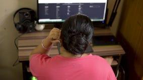 桃红色T恤杉工作的印度亚裔白种人妇女在下巴的台式计算机手上 浏览议院的妻子读互联网网站博克 股票录像