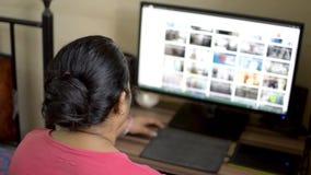 桃红色T恤杉工作的印度亚裔白种人妇女在台式计算机计算机上在家 浏览议院的妻子读互联网网站 股票录像
