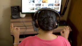 桃红色T恤杉的听印度亚裔白种人妇女的女孩在家享用在台式计算机计算机上的音乐佩带的耳机 ?? 股票视频