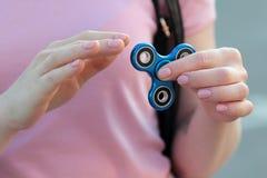 桃红色T恤杉的女孩在手在街道上,妇女使用与一个普遍的坐立不安锭床工人玩具的, anxiet上扮演蓝色金属锭床工人 免版税图库摄影