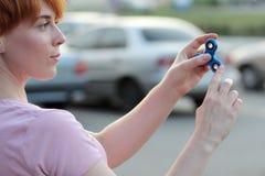 桃红色T恤杉的女孩在手在街道上,妇女使用与一个普遍的坐立不安锭床工人玩具的, anxiet上扮演蓝色金属锭床工人 图库摄影