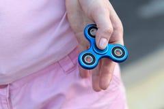 桃红色T恤杉的女孩在手在街道上,妇女使用与一个普遍的坐立不安锭床工人玩具的, anxiet上扮演蓝色金属锭床工人 库存照片