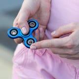 桃红色T恤杉的女孩在手在街道上,妇女使用与一个普遍的坐立不安锭床工人玩具的, anxiet上扮演蓝色金属锭床工人 库存图片