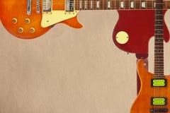 桃花心木和镶有钻石的旭日形首饰的电吉他和和后面在概略的纸板背景的吉他身体,与大量拷贝空间 免版税库存照片