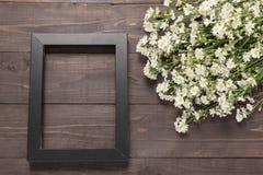 画框和切削刀花在木背景 免版税库存照片