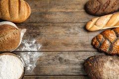 框架做了用新鲜面包在木背景,平的位置 图库摄影