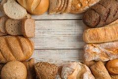 框架做了用新鲜面包在木背景,平的位置 免版税库存图片