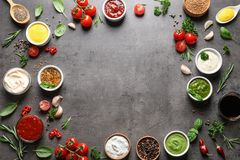 框架做用不同的调味汁和成份在灰色背景,平的位置 免版税库存图片