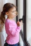 框架女孩把柄在立场视窗附近暂挂 免版税库存图片