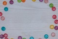 框架用色的糖果wodden白色桌 平的位置,顶视图 库存照片