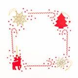 框架由圣诞节装饰、红色五彩纸屑和棒棒糖制成在白色背景 平的位置,顶视图 概念新年度 免版税图库摄影