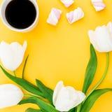 框架由白色郁金香做成开花与杯子咖啡和蛋白软糖在黄色背景 背景植物的圈子盘旋公司使最大的徽标环境美化的冷静花卉花花园庭院中间完善界面固定的空间白色的构成概念 平的位置,顶视图 免版税库存照片