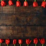 框架由红色郁金香做成在黑暗的木背景 库存图片