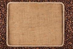 框架由绳索制成用咖啡豆在麻袋布 库存图片