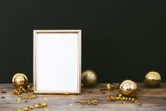 框架的嘲笑在与圣诞节装饰闪烁雪花、中看不中用的物品、响铃、蛇纹石和星co的木土气黑暗的背景 库存图片