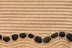 框架说谎由黑的石头做成锯齿形地,在波浪沙子 免版税库存图片