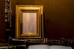 画框静物画在木桌上的与单簧管 图库摄影