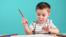 桌凹道的被启发的小男孩与铅笔,隔绝在蓝色 股票录像