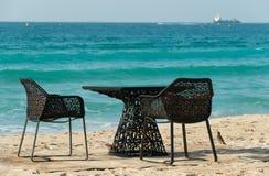 黑桌和两把椅子在海滩 库存图片