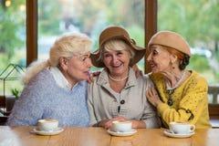 桌微笑的资深妇女 免版税库存图片