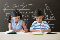 桌文字的学生反对有教育和学校图表的灰色黑板 免版税图库摄影