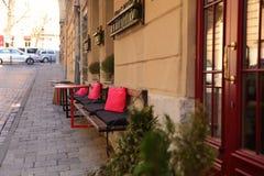桌是明亮的,并且与红色枕头的长凳是在一条狭窄的街道上的一个咖啡馆 免版税库存图片