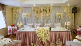 桌的婚礼装饰在一家餐馆,宴会的 由真正的花做的婚礼装饰 背景装饰高雅花粉红色浪漫婚礼 股票录像