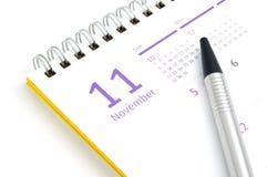 桌面日历和笔在白色背景 免版税库存照片