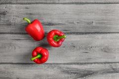 桌面看法-在灰色木书桌上的三个明亮的红色甜椒 库存照片