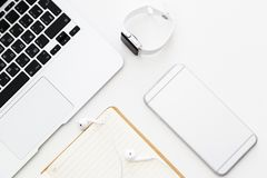 桌面项目:膝上型计算机,笔记本,耳机,手机,说谎在白色背景的巧妙的手表 平的位置,顶视图,在头顶上, 免版税库存图片