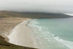 桑德斯在一堆云的海岛海滩下 免版税库存照片