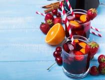 桑格里酒用在一块玻璃的莓果在蓝色木背景 库存图片