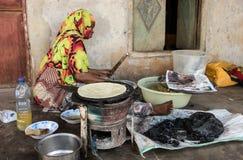 桑给巴尔,坦桑尼亚,东非- 2017年6月20日:非洲妇女烘烤传统面包蛋糕-在一个火炉的小面包干与c 免版税库存照片