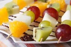 桔子、猕猴桃、葡萄和梨在水平串的宏指令 免版税库存图片