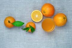 桔子、蜜桔和橙汁在一块玻璃,在一亚麻制tabl 免版税库存图片