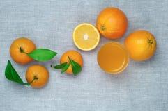 桔子、蜜桔和橙汁在一块玻璃,在一亚麻制tabl 免版税库存照片
