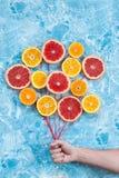 桔子、蜜桔和葡萄柚在契合作为气球,拿着串的手 免版税库存照片