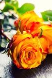 桔子上升了 上升了黄色 在花岗岩背景的几朵橙色玫瑰 免版税库存照片